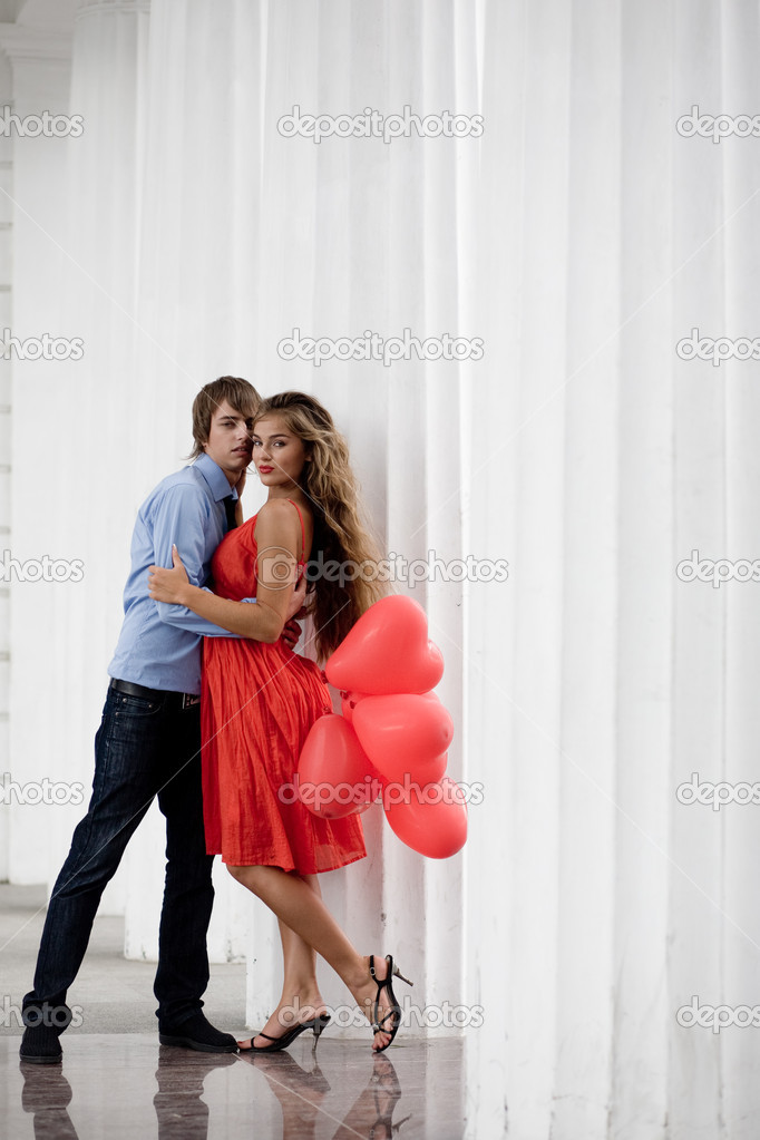 Young couple embracing among white columns and holding bunch of baloons-hearts — Stock Photo #1246897
