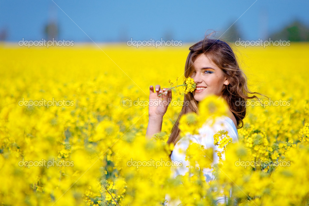 Nice girl holding flower in rape field — Stock fotografie #1247074