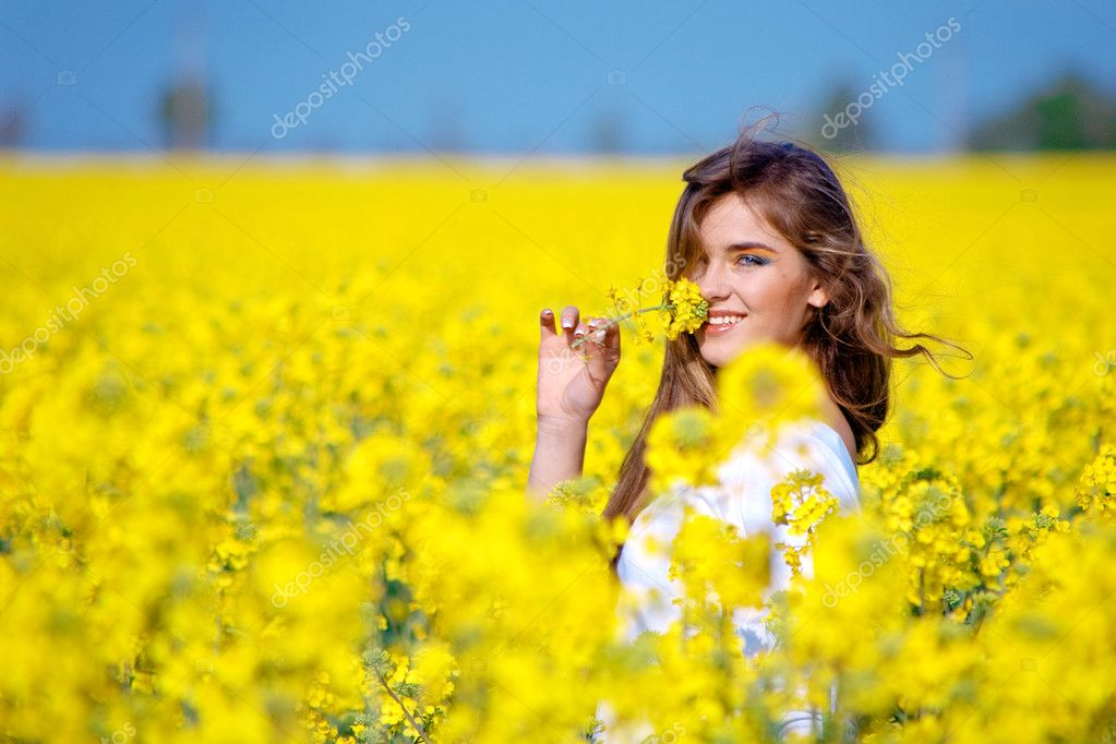 Nice girl holding flower in rape field — Stockfoto #1247074