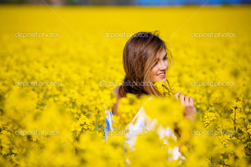 Young girl in field of flowers from back. — Stock Photo #1247086