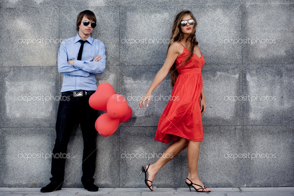 Young couple in sunglasses posing near wall — Stok fotoğraf #1247130