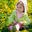 Child among dandelions — Stockfoto