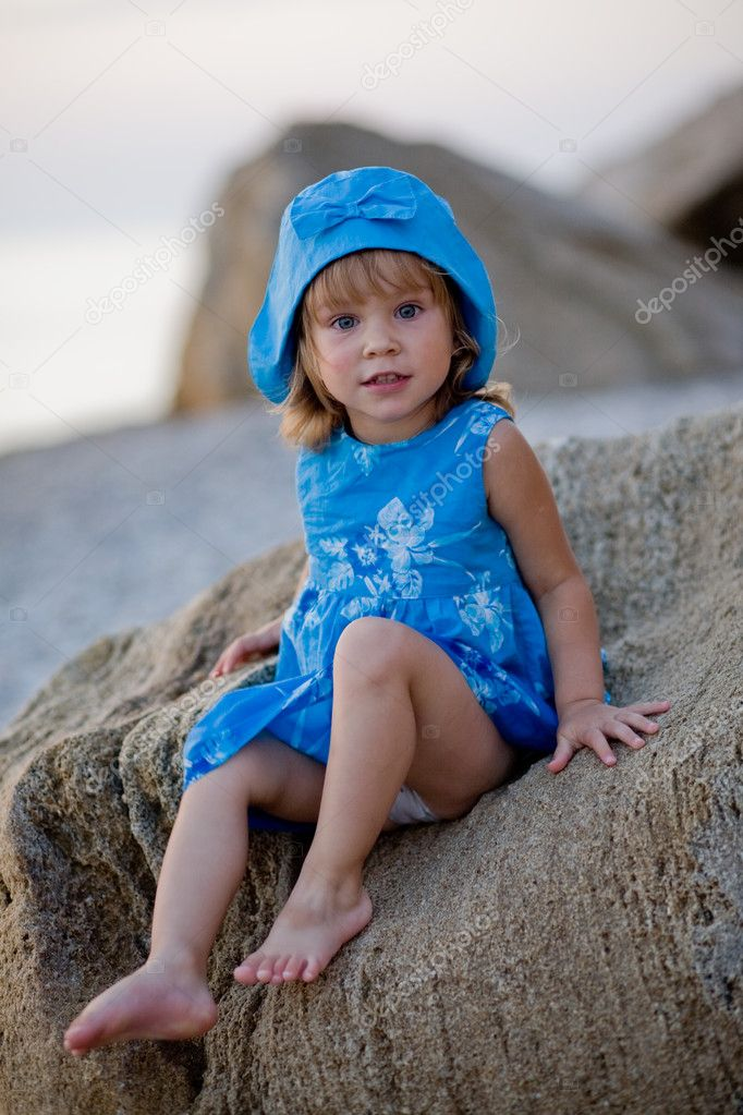 Baby girl in blue dress and hat sitting on stones at sunset beach  Stock Photo #1251256