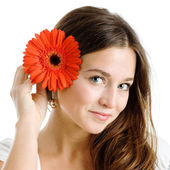Beautiful woman with a bright red flower — Stock Photo