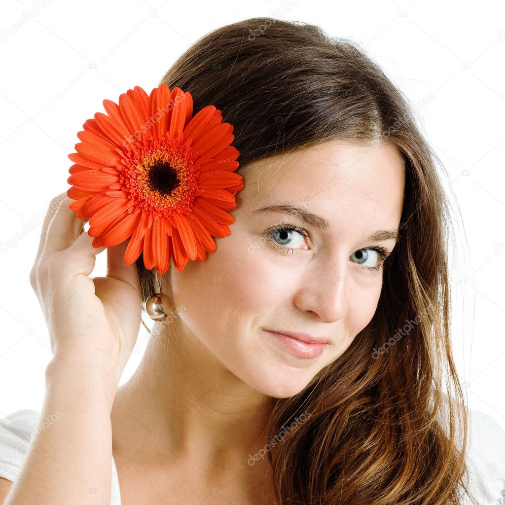 A smiling beautiful young woman in a white dress with a bright red flower near her face  — Stock Photo #1188423