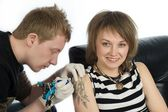 An image of man and woman making tatoo — Stock Photo