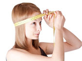 Young girl measures a head — Stock Photo