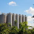 Twelve high metal tower silos on plant - Stock Photo