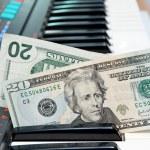 Dollar bills in electric organ keyboard — Stock Photo