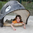 Cute little girl lies in turtle shell — Stock Photo