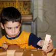 Cute little boy plays with wooden bricks — Stock Photo