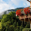 Alpine chalet balcony with flowers - Stock Photo