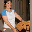 Smiling  woman riding a hobby-horse — Stock Photo