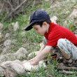 Little boy squatting on stones outdoors — Stock Photo