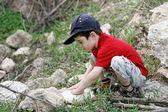 Little boy squatting on stones outdoors — Stock Photo