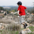 Little boy jumps from the stone outdoor — Stock Photo