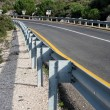 Stock Photo: Road in forest with guardrail
