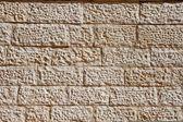 Wall built of beige stone blocks — Stock Photo