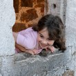Smiling girl leans out of castle window - Stock Photo