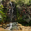Waterfall falls over black basalt rocks - Stock Photo
