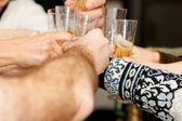 Hands clinking glasses — Stock Photo