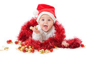 Little boy wearing a Santa hat and playi — Stock Photo