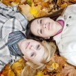 Two lying girls in leaves — Stock Photo