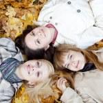 Three girls lying in leaves — Stock Photo