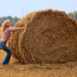 Haystack and girl on the meadow in sunny - Stock Photo
