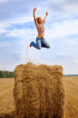 Girl jumping up on straw roll — Stock Photo