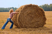 Haystack and girl on the meadow in sunny — Stock Photo