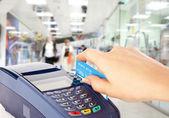 Mão humana segurando o cartão de plástico em pagara — Foto Stock