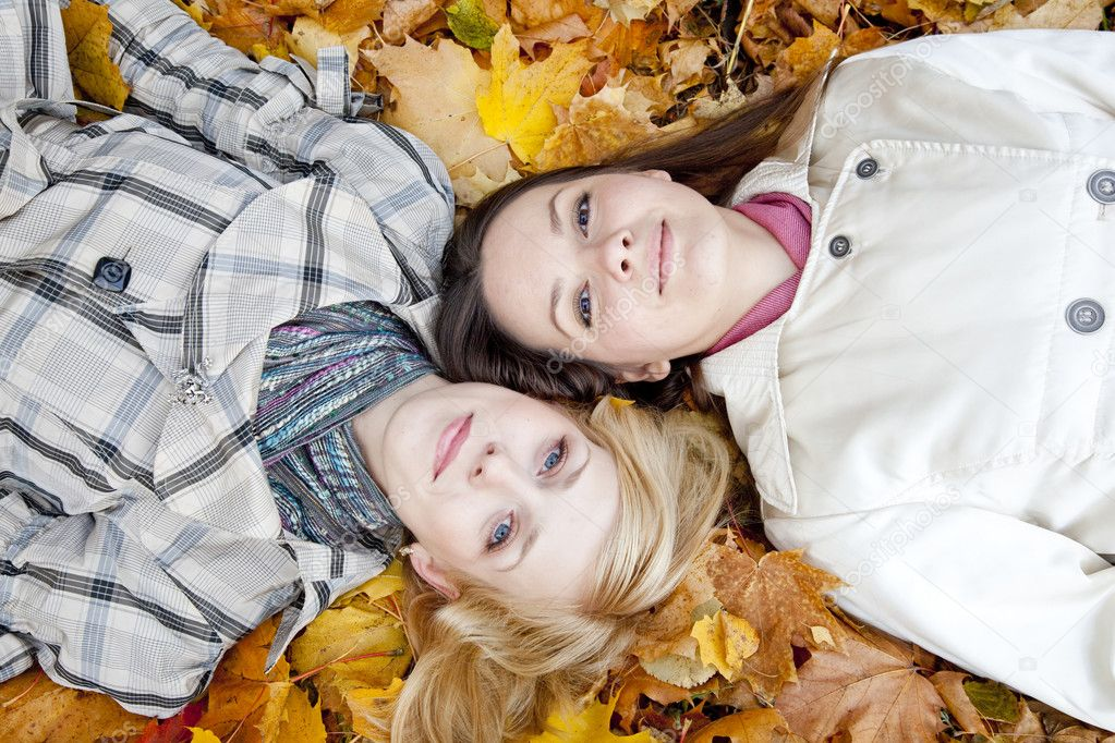 Two young lying girls in leaves — Stock Photo #1250394