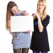Two teenage girls with card for text — Stock Photo