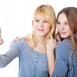 Stock Photo: Two teenage girls photographing on