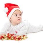 Little boy wearing a Santa hat and playi — Stock Photo