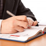 Businessman hands writing in organizer — Stock Photo