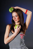 Smiling woman with two green apples — Stock Photo