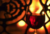 Glass of wine in front of the fireplace — Stock Photo