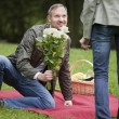 Man meets woman with flowers — Stock Photo
