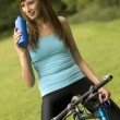 Thirsty woman on bike — Stock Photo