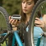 Постер, плакат: Woman repairs bike