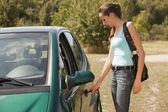 Woman with key open car door — Stock Photo