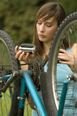 Woman repairs bike — Stock Photo