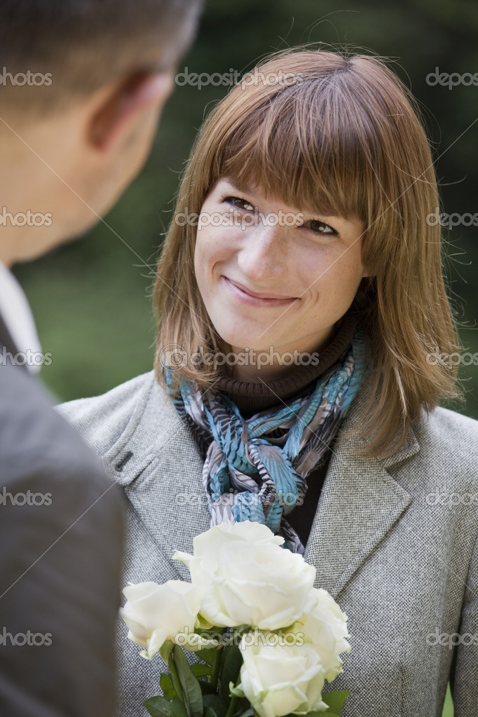 Woman with flowers meets her boyfriend in a city park — Stock Photo #1172515