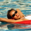 Woman swimming on an air mattress - ストック写真