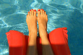 Woman feet in the pool — Stock Photo