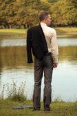 Uomo con la giacca sulla riva — Foto Stock