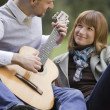 Stock Photo: Man playing acoustic guitar outdoors