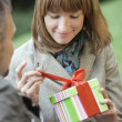 Woman opening gift box outdoors — Stock Photo